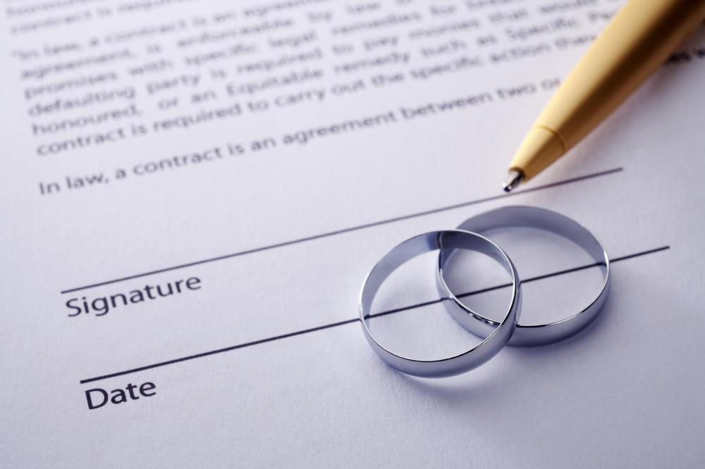 A marriage contract with a pen and two rings on top
