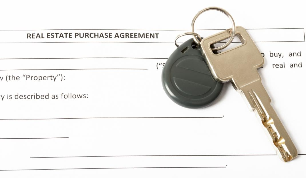 Real estate contract with house key on top