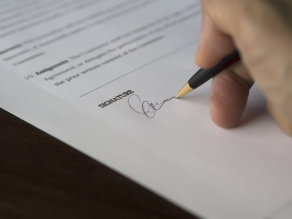 A buyer signing a real estate agreement