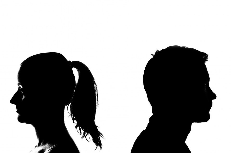 Silhouette of man and woman standing apart