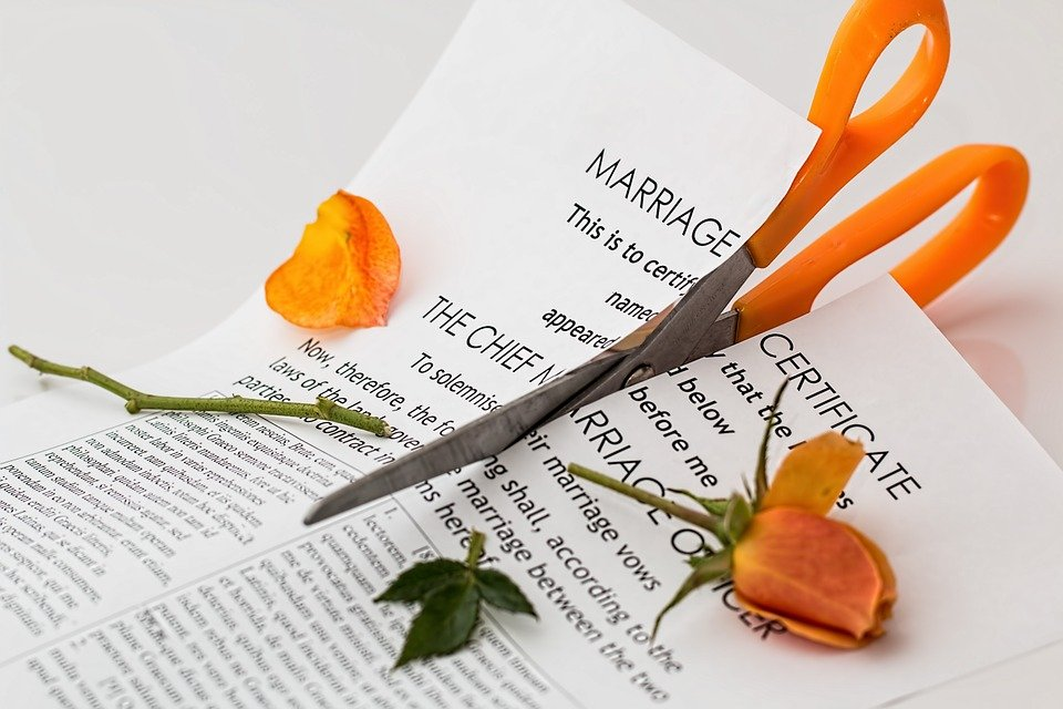 marriage certificate being cut by a pair of scissors