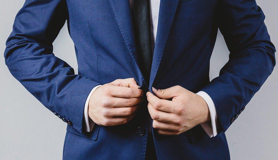 man buttoning his blue blazer